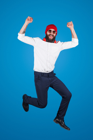 Colorful hipster in formal outfit jumping up