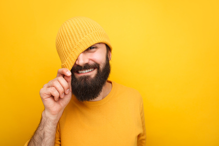 Handsome playful hipster in colorful hat