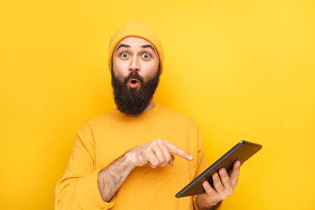 Expressive guy pointing at tablet