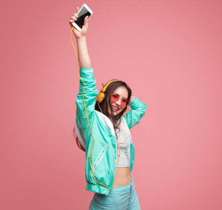 Young woman with smartphone dancing Stock Photo