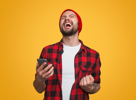 Happy male with smartphone celebrating success Stock fotó
