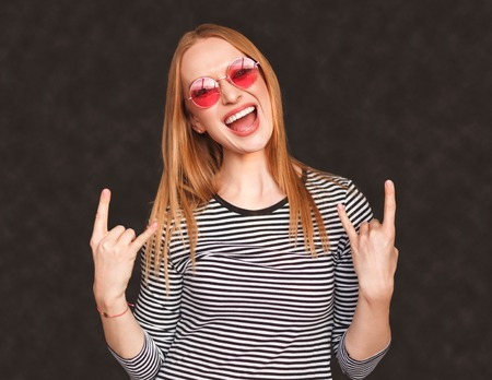 Excited young woman showing rock gesture Stock Photo