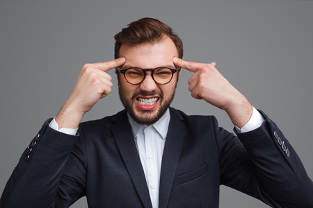 Angry businessman squeezing head with fingers Stock Photo