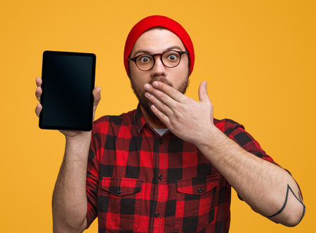 Amazed man with tablet covering mouth Фото со стока