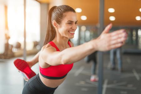 Cheerful woman training in gym