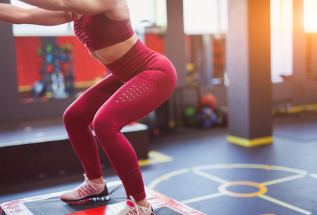 Crop sportswoman doing squats in gym