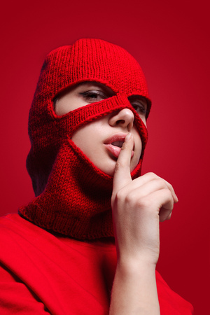 Woman in mask showing silence gesture