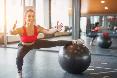 Cheerful woman exercising with Swiss ball