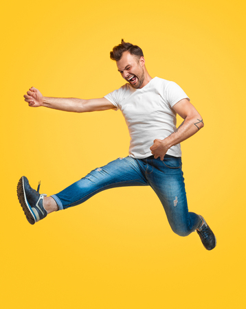 Man jumping and pretending to play guitar Stock Photo