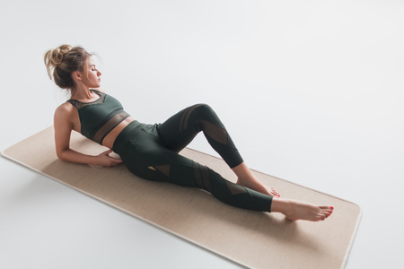 Relaxing woman in sportswear lying on mat