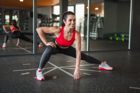 Fröhliche sportliche Frau macht seitliche Ausfallschritte
