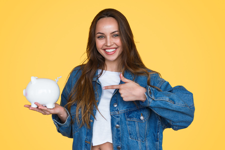 Happy girl showing white piggy bank