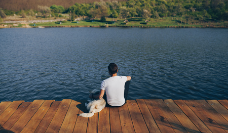 Anonymous man with dog sitting on pier