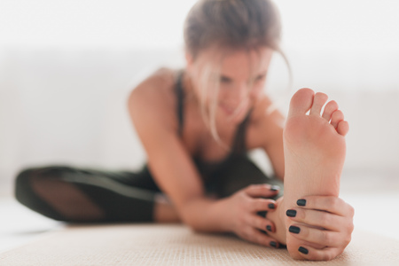 Stretching barefoot woman on mat