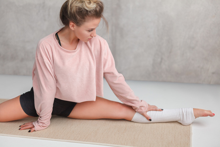 Stretching young woman on mat
