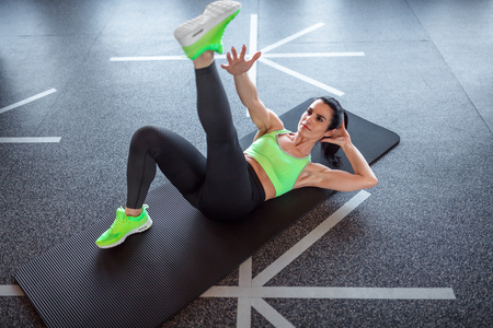 Woman performing exercise on gym floor