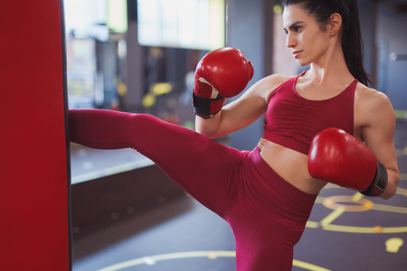 Modern adult sportswoman boxing in gym
