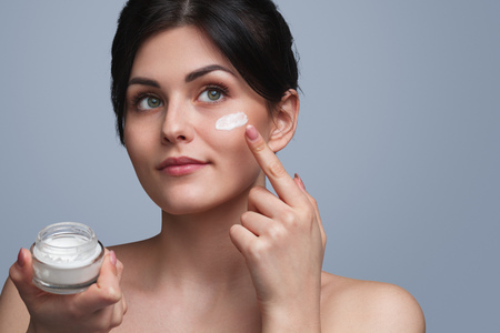 Young woman smearing cream on face