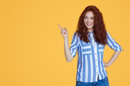 Stilvolles Teenager-Mädchen, das nach oben zeigt Standard-Bild