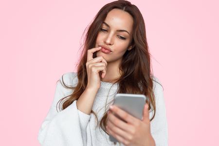 Pretty pensive woman watching phone