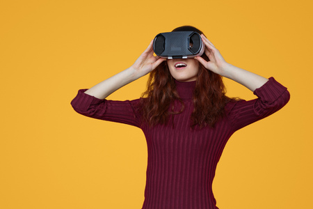 Excited woman experiencing virtual reality in headset
