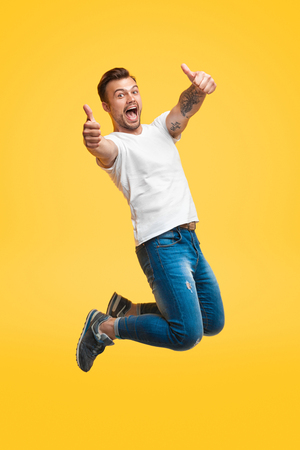 Excited man jumping and gesturing thumb up Archivio Fotografico - 115929311