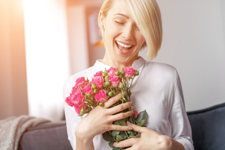 Pleased female with bunch of flowers