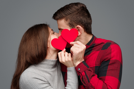 Young couple kissing behind hearts Imagens