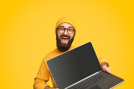 Smiling man promoting modern laptop Stockfoto