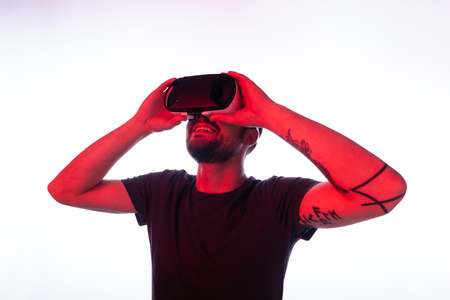Tattooed man in VR glasses looking up Stock Photo