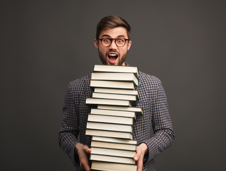 Student with stack of books screaming