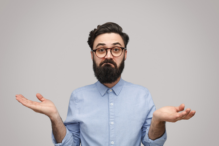 Doubtful bearded man shrugging with shoulders Stock Photo