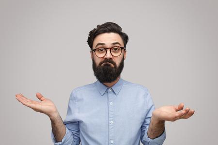 Zweifelnder bärtiger Mann zuckt mit den Schultern