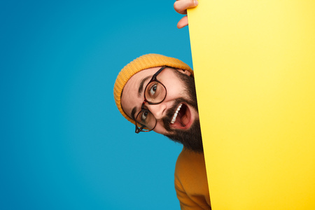 Cheerful man peeking out from behind poster Stock Photo