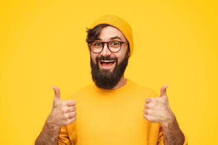 Brodaty mężczyzna gestykuluje kciukiem w górę
