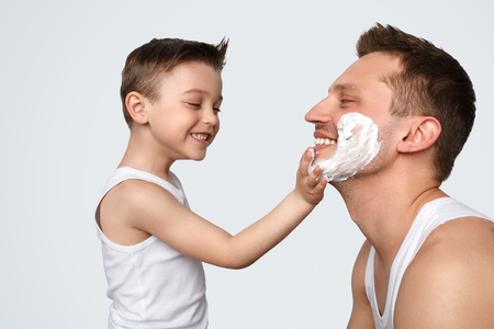 Son helping father with shaving Stock Photo