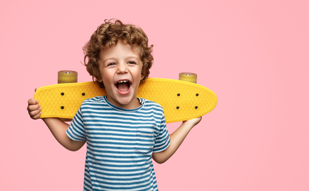 Cute boy with yellow skateboard Banque d'images