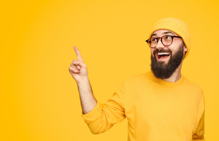 Cheerful hipster pointing up