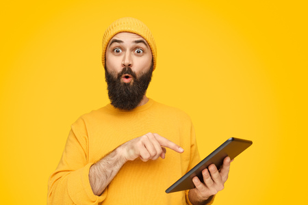 Überraschter Mann, der auf Tablette zeigt