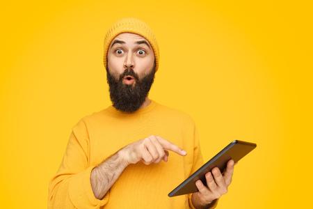 Hombre sorprendido apuntando a la tableta