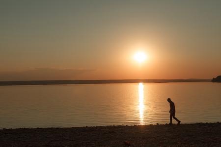 Wandering man on tranquil seashore Фото со стока