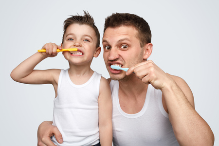 Funny father and son brushing teeth