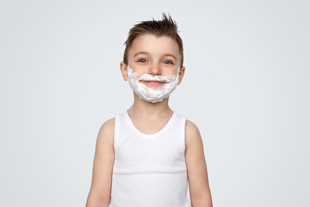 Content boy with shave foam on face Banco de Imagens
