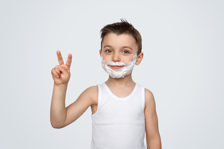 Boy with shaving foam showing V sign