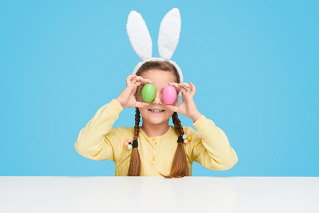 Funny girl with Easter eggs near eyes