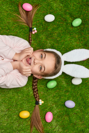Cute girl lying on grass with Easter eggs Stock Photo