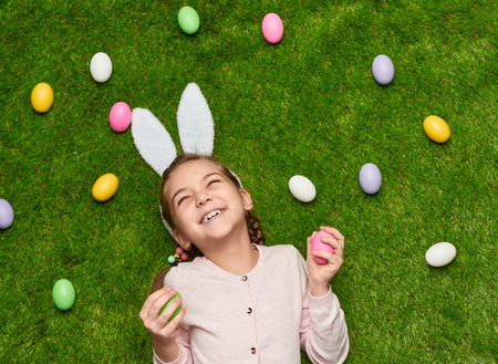Cheerful girls with Easter eggs on lawn Stockfoto