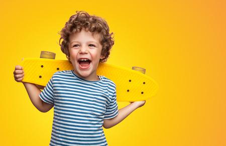 Heller lockiger Junge mit buntem Longboard Standard-Bild