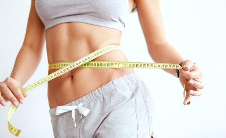 Mujer delgada de cultivo midiendo la línea de la cintura
