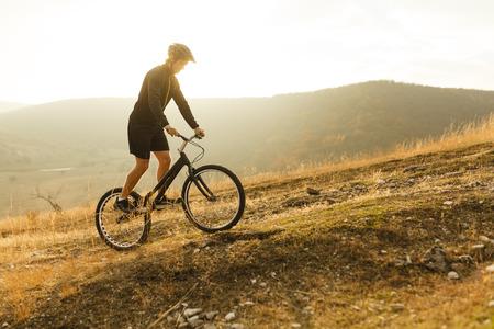 Sportsman standing on bike on hill Stock Photo